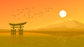 Flying birds against orange sunset ocer coast Japanese gate (Tor Royalty Free Stock Photo