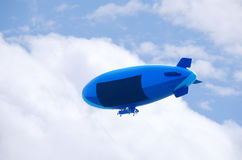 Flying blimp with blank advertising sign area. Flying colorful blimp with a blank advertising sign area to accommodate your message. Fluffy clouds and blue sky royalty free stock image