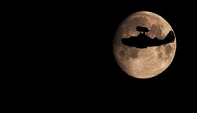 Flying boat plane silhouette on the whole Moon surface background Stock Image