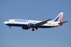 Flying the Boeing 737-400 (EI-CZK) company Transaero Airlines on the background of blue sky Stock Photos