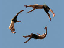 Flying boys. A cirlcle of three flying young athletic men Royalty Free Stock Photo