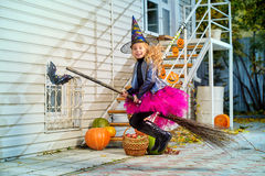 Flying on a broomstick. Pretty little girl in a costume of witch with her magic broom celebrating halloween. Trick or treat. Halloween party Stock Image