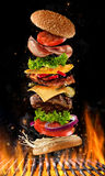 Flying burger ingredients above grill Royalty Free Stock Image