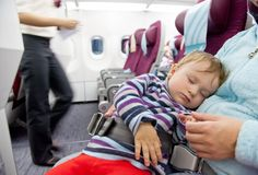 Mother and sleeping two year old baby girl travel on airplane stock photo