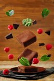 Flying Chocolate cake Brownie with mint and raspberries Stock Photo