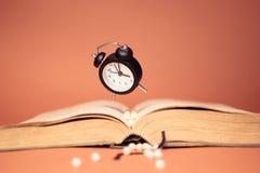 Flying clock and book on orange background. stock photo