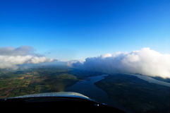 Flying With The Clouds. A view out of the front of a cessna aircraft with clouds directly ahead and the ground and rivers below Stock Images