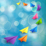 Flying color paper planes on the blue blurred background Royalty Free Stock Images