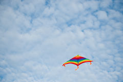 Flying colorful kite on cloudy blue sky background. Flying colorful kite on beautiful cloudy blue sky background Royalty Free Stock Photos