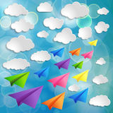 Flying colorful paper airplanes with clouds on the blue b Royalty Free Stock Images