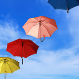 Flying colorful umbrellas blue sky background stock images