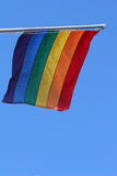 Flying colors. Flag in rainbow colors flying against a clear blue sky Stock Photos