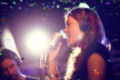 Composite image of flying colours. Flying colours against female singer at nightclub Stock Images
