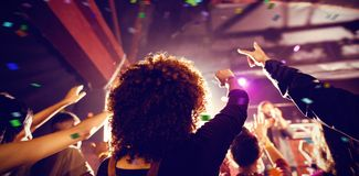 Composite image of flying colours. Flying colours against people enjoying music concert at nightclub Royalty Free Stock Images
