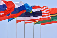 Flying countries flag. Different countries national flags getting together under blue sky, shown as worldwide, country, and international communication or Stock Photos