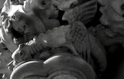 Flying creature. Shot in black and white, detail on a capital with an sculpture representing a winged creature on the facade of this historic building, set in Royalty Free Stock Images