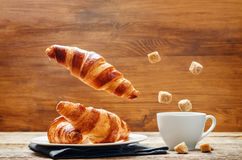 Flying croissant with coffee Stock Photos