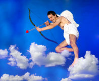 Flying Cupid. Cupid with bow flying over clouds stock photography