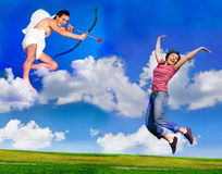 Flying Cupid. Cupid aiming his bow at young happy woman stock photo