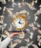 Flying dollar bills and alarm clock Stock Images
