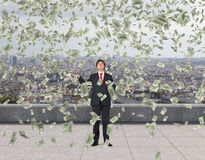 Flying dollar bills. Businessman standing on roof and catching flying dollar bills Royalty Free Stock Image
