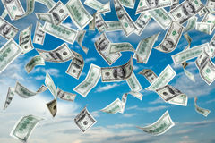 Flying dollars. Falling dollars from the blue sky Stock Images