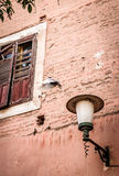 Flying Dove in front of brick wall. With lamp and window with shutters Royalty Free Stock Photography
