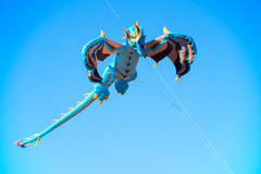 Flying Dragon Kite. A big flying kite in shape of a dragon with the blue sky in the background royalty free stock photo