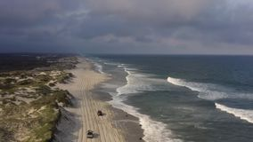 Aerial view of sandy road on the oceans beach. 4k. Flying with drone above ocean beach road. Evening time, 4x4 vehicle are driving on the beach. 4wd stock footage
