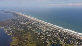 Aerial view of town, ocean and beach. 4k. Flying with drone along coast in Avon, NC, USA. Aerial footage of ocean, beach and city stock video footage
