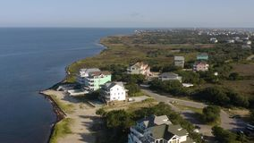 Aerial view of town, ocean and beach. 4k. Flying with drone along coast in Avon, NC, USA. Aerial footage of ocean, beach and city stock footage