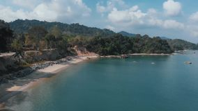 Flying drone along a sandy beach with a high cliff. Langkawi, Malaysia stock video footage