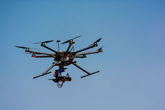 Flying drone with a camera. On blue sky background stock photography