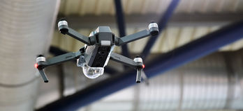 Flying drone with camera. Quadcopter flying indoor. Professional small drone with video camera hanging in the air. Concept: an innovative high-tech Royalty Free Stock Photography