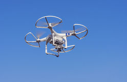 Flying drone with camera. Drone flying in the sky with a mounted digital camera used for photographing and filming Stock Photos