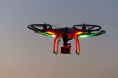 Flying drone with camera on the sky at sunset Stock Photos