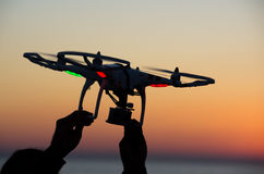 Flying drone with camera on the sky at sunset Stock Image
