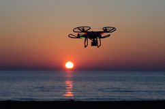 Flying drone with camera on the sky at sunset Royalty Free Stock Photo