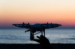 Flying drone with camera on the sky at sunset Stock Images