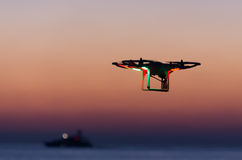 Flying drone with camera on the sky at sunset Royalty Free Stock Image