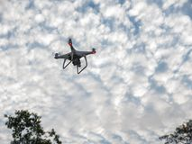 Flying drone with digital camera. Drone copter is flying with digital camera on sky background Stock Photo