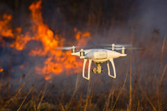 Flying drone in a fire. The drone flies against the background of a spring forest fire Stock Photo