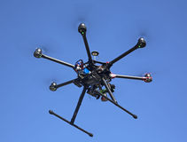 Flying drone. A flying hexacopter with spinning propellers and without a camera shot from below with the blue sky on the background Stock Photo