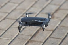 A flying drone lands on the ground. Mid shot royalty free stock photography