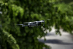 Flying Drone. Remote Controlled Flying Drone Capturing High Resolution Video In Front Of Trees royalty free stock photography