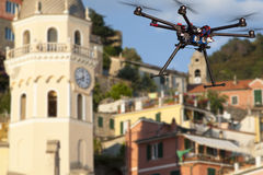 Flying drone in the skies of Vernaza. A flying drone without a camera with a blured old town in the background Stock Photo
