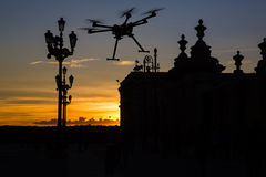 Flying drone in the sunset skies. A silhouette of a flying drone with a dramatic sunset and elements of European architecture in the background Stock Photography