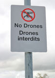 Flying Drones Not Permitted Sign. A sign warns in English and French that flying drones is not permitted royalty free stock photos