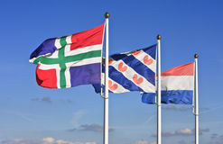 Flying dutch flags. From left to right the fluttering flags of the dutch province Groningen, the dutch province Friesland and the national flag of the Stock Image
