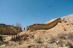 Free Flying Eagles Over The Ancient Fortress Wall. The Gunib Fortress Is A Historical Monument Of Dagestan Stock Photos - 218039793